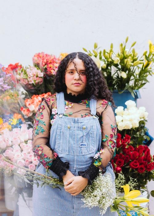 Lido Pimienta fotografiert inmitten eines Blumenmeers: Die Kolumbianerin setzt sich als Power-Frau in der Musik gegen Rassismus und Diskriminierung ein.